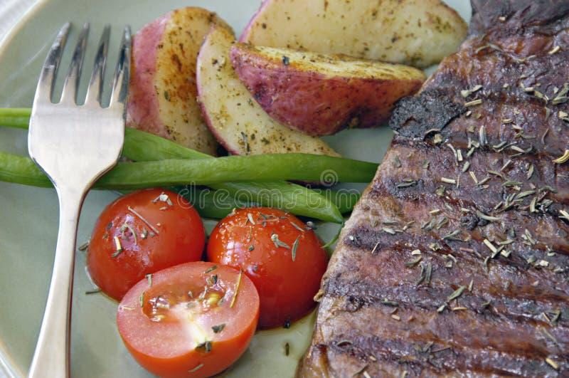 Bife com batatas, tomates, e feijões foto de stock