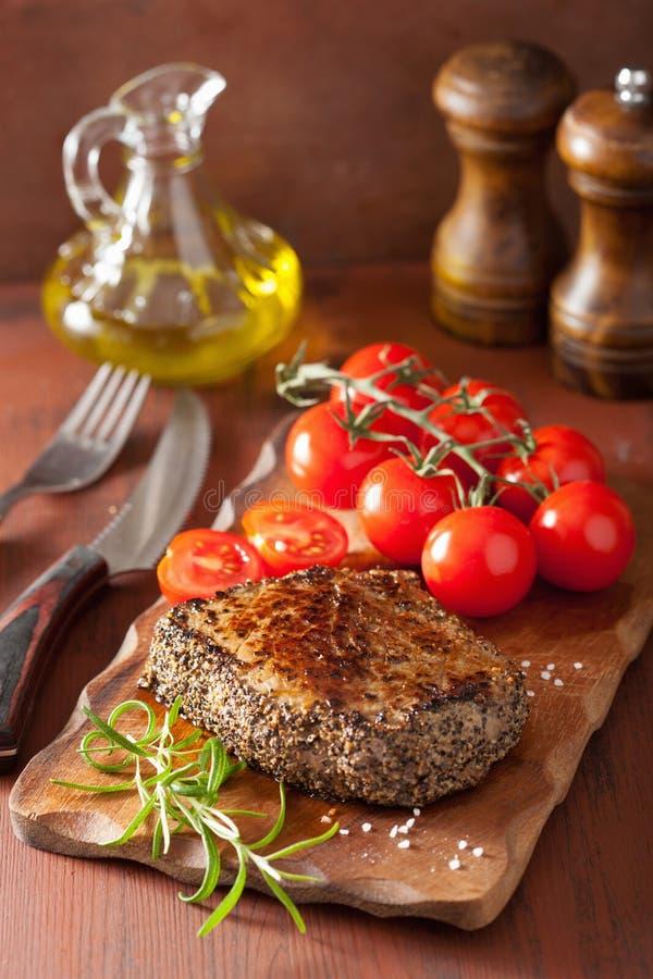 Bife com especiarias e alecrins no fundo de madeira fotos de stock
