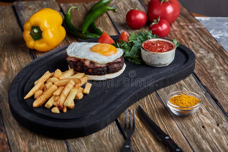 Bife com ovo e salada dos verdes e dos vegetais Fundo de madeira, ajuste da tabela, jantando muito bem fotografia de stock royalty free