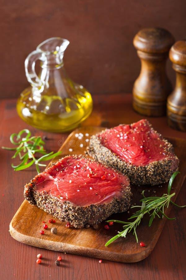 Bife cru com especiarias e alecrins no fundo de madeira imagem de stock royalty free
