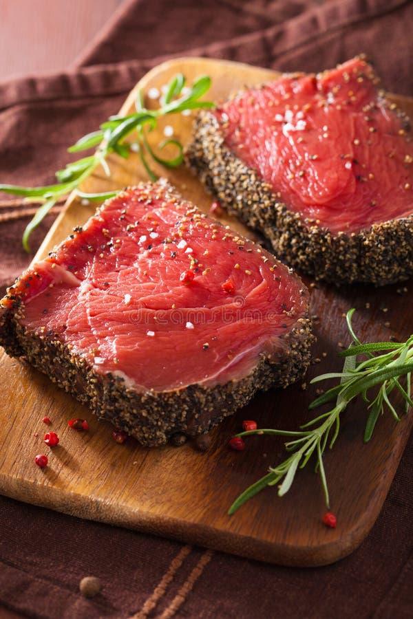 Bife cru com especiarias e alecrins no fundo de madeira fotografia de stock