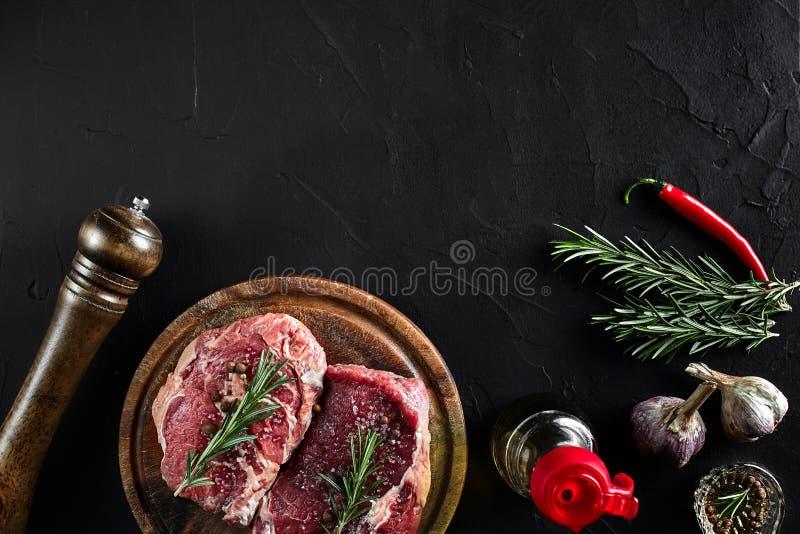 Bife cru com especiarias e ingredientes para cozinhar na placa de corte e no fundo da ardósia Vista superior fotografia de stock royalty free
