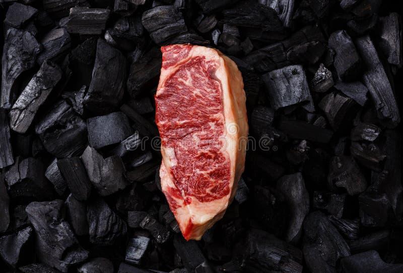 Bife cru de Striploin no carvão vegetal foto de stock