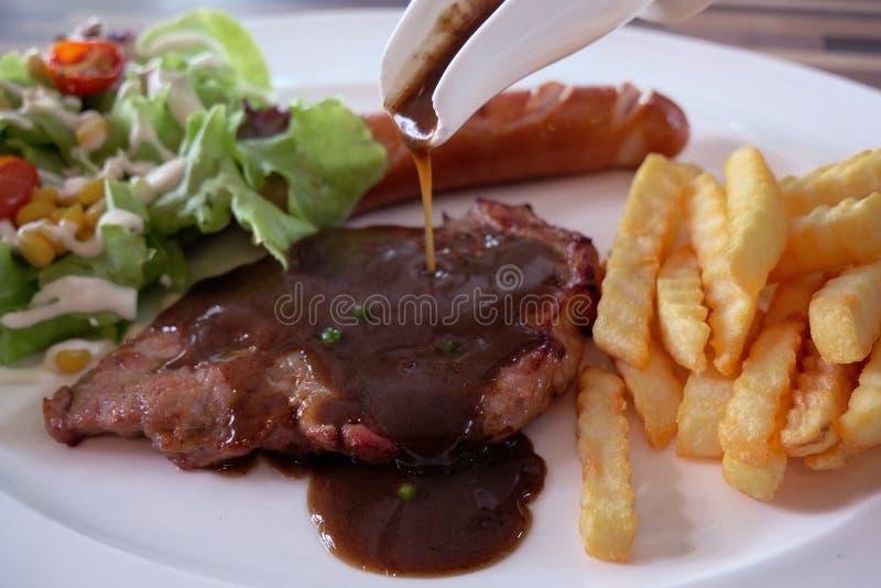 Bife da carne de porco com molho e batatas fritas na placa fotos de stock royalty free