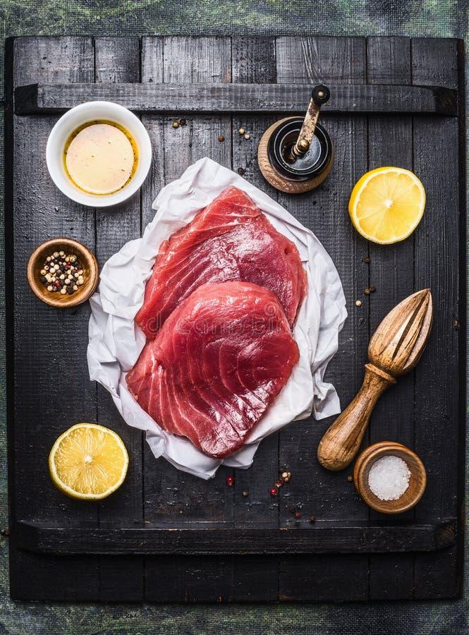 Bife de atum cru com limão, óleo e ingredientes para cozinhar no fundo de madeira escuro fotografia de stock