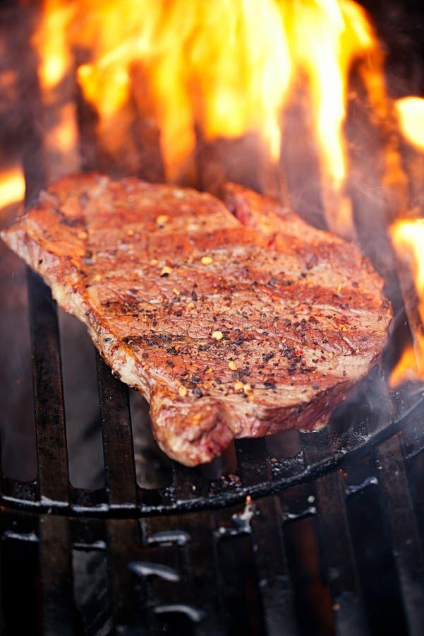 Bife de carne assada do olho do reforço de Ribeye na grade do assado do BBQ com chama foto de stock