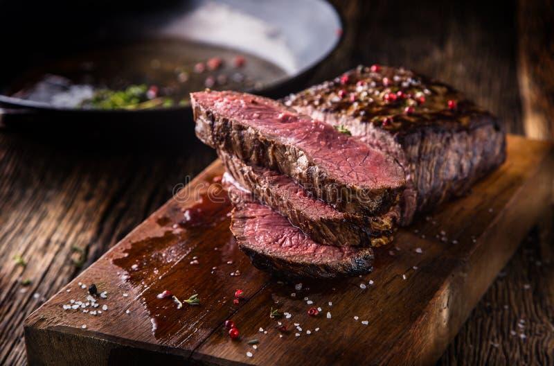 Bife de carne Fatias médias suculentas do bife de Rib Eye na placa de madeira com as especiarias e o sal das ervas da forquilha e foto de stock royalty free