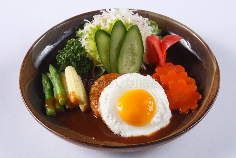Bife de Hamburgo do japonês com o ovo frito e o molho isolados no whit fotografia de stock