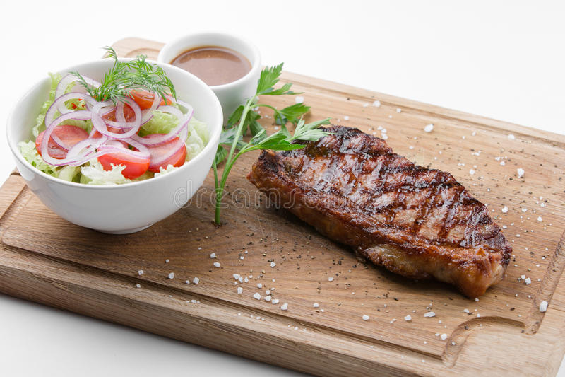 Bife de New York com salada vegetal na placa de corte de madeira imagem de stock royalty free