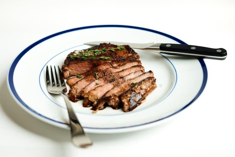 Bife de Ribeye em Rim Plate azul fotografia de stock