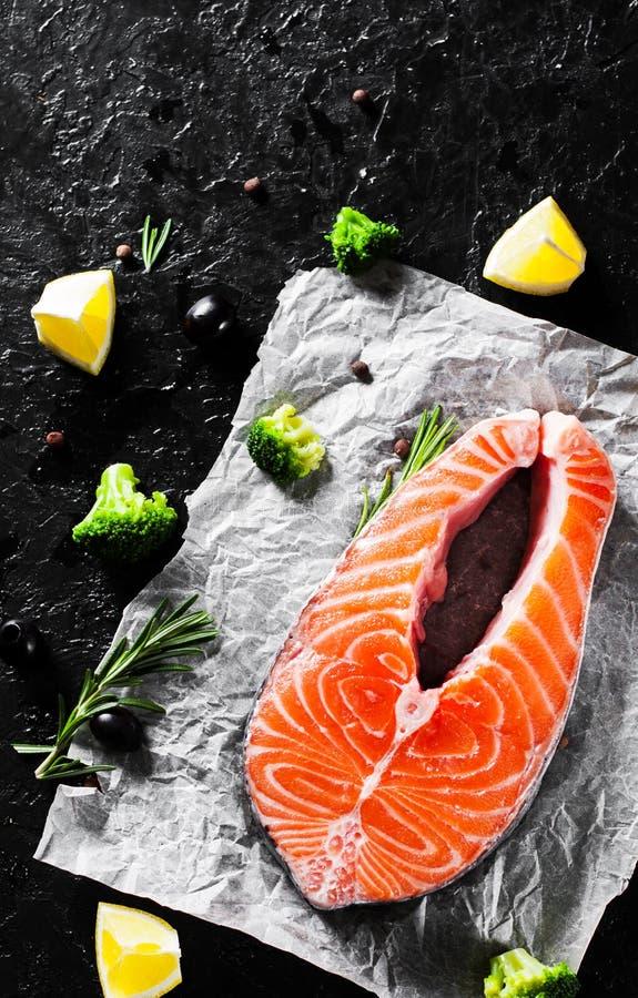 Bife de salmões cru fresco com brócolis, limão, azeitona, pimenta e as ervas aromáticas no fundo escuro Com espaço da cópia fotografia de stock royalty free