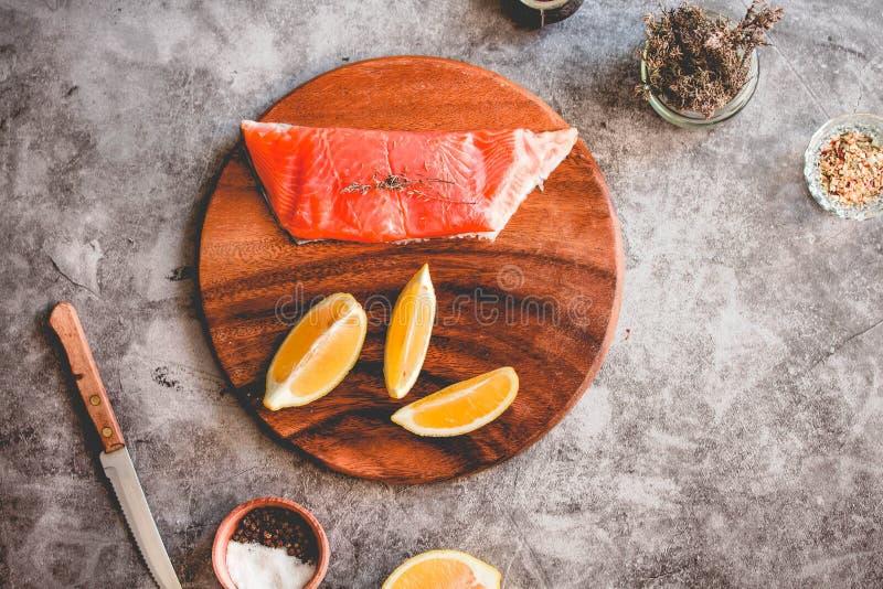 Bife de salmões delicioso cru Pimenta, sal, paz do limão e alecrins em uma placa de madeira Prepere para cozer fotografia de stock