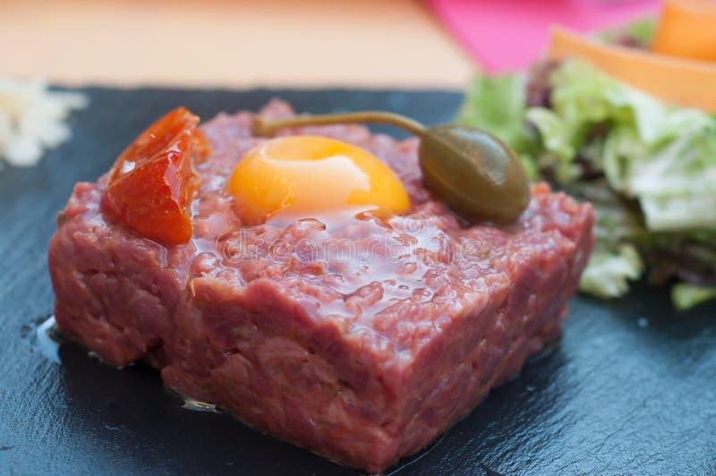 Bife de tártaro com ovo e alcaparras no quadro no restaurante imagens de stock