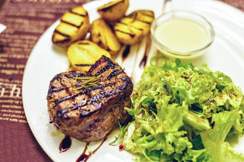 Bife delicioso com molho branco, batatas e alface imagens de stock royalty free