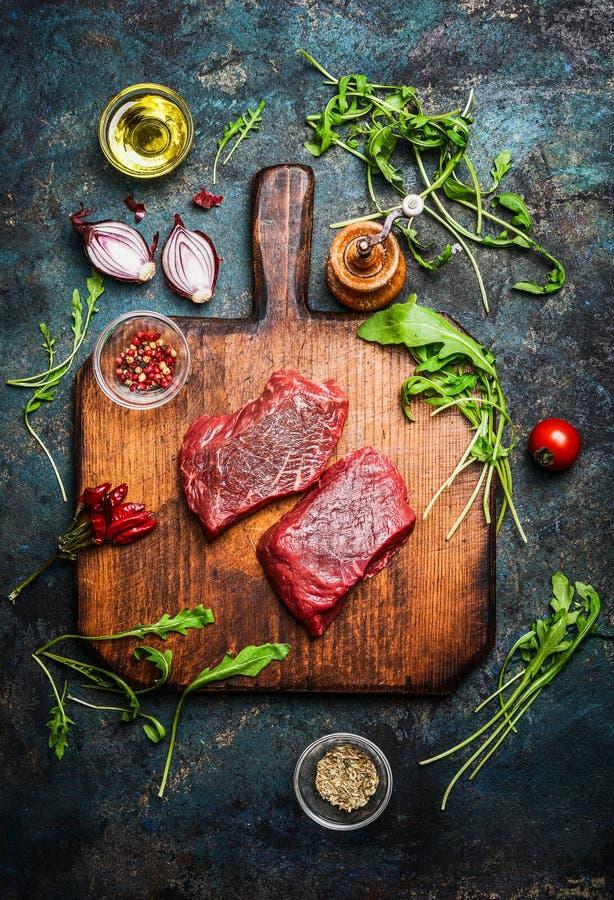 Bife delicioso na placa de corte do vintage com os vários ingredientes frescos para o cozimento saboroso no fundo de madeira rúst fotos de stock royalty free