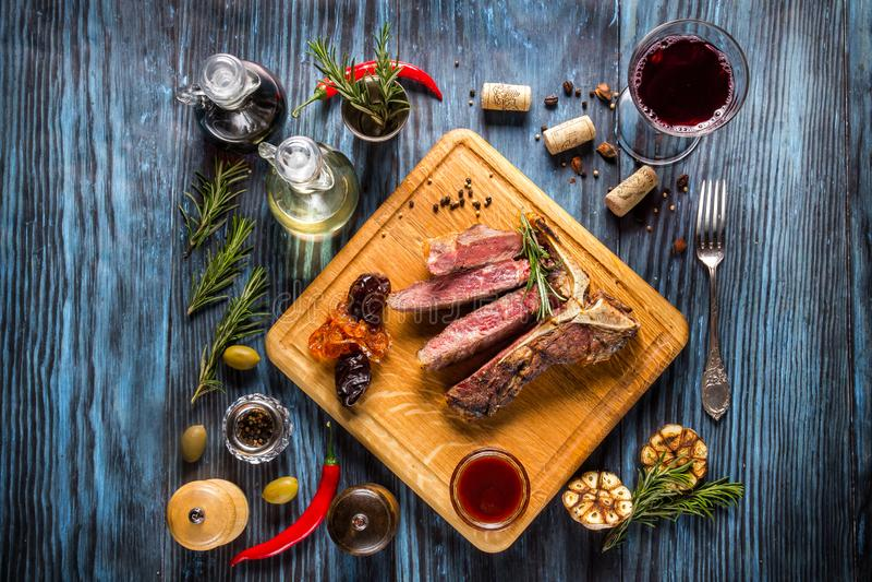 Bife do lombo grelhado raro médio cortado no fundo de madeira rústico com alecrins e especiarias imagens de stock