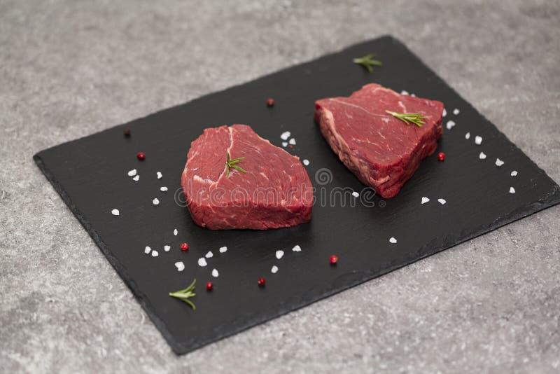 Bife e especiarias crus na placa da ardósia Carne crua no fundo preto imagem de stock