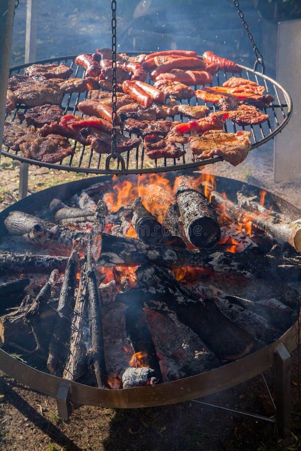 Bife e salsichas do mandril que estão sendo grelhados foto de stock
