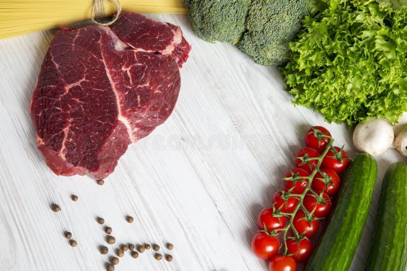 Bife fresco da carne crua com tomates de cereja, espaguetes, alimento natural Fundo de madeira branco Copie o espaço imagens de stock royalty free