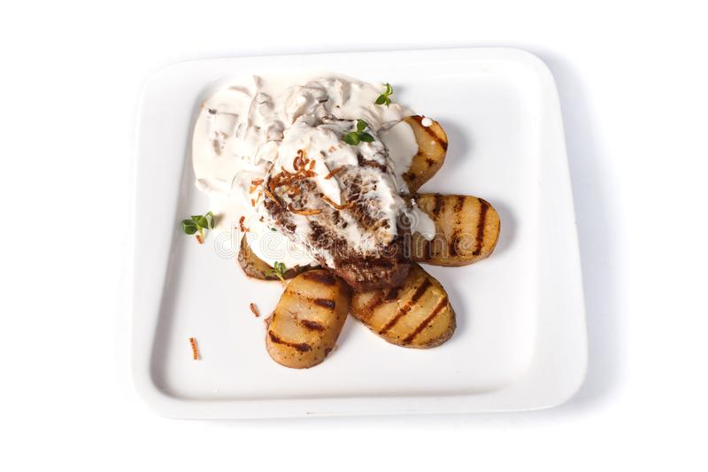 Bife fritado com batatas em um potenciômetro branco em uma placa quadrada em um fundo branco isolado imagem de stock