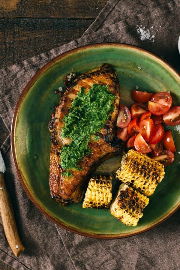 Bife grelhado com molho e tomates do chimichurri sobre Ta de madeira fotos de stock royalty free