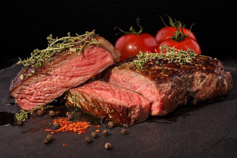 Bife grelhado cortado com as especiarias na laje da ardósia imagens de stock