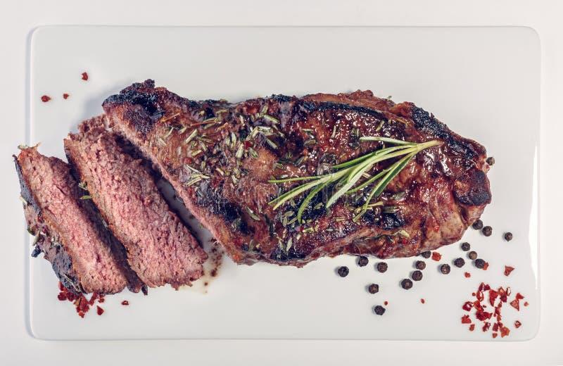 Bife grelhado cortado na placa branca fotografia de stock