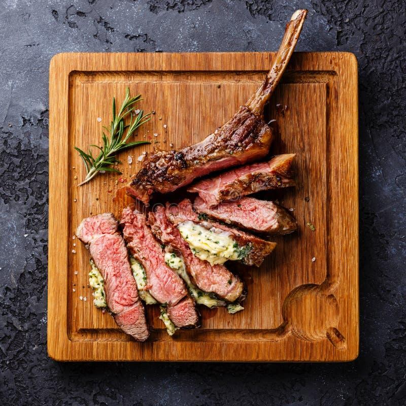 Bife grelhado cortado no reforço da vitela do osso com manteiga de erva imagem de stock