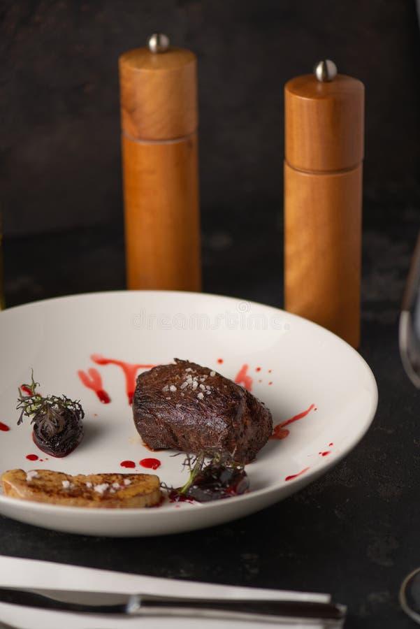 Bife grelhado delicioso com um vidro de vinho Restaurante imagens de stock royalty free