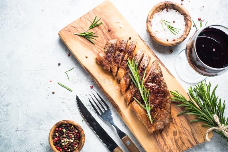 Bife grelhado do striploin da carne com vidro de vinho tinto foto de stock