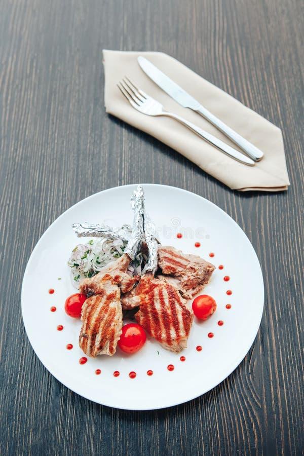 Bife grelhado em um osso com tomates em uma placa branca Pratos quentes da carne fotos de stock royalty free