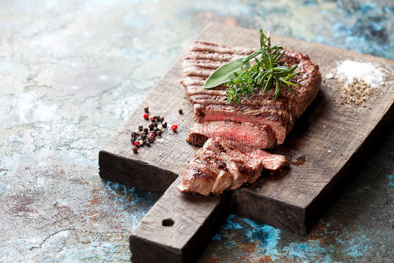 Bife grelhado raro médio cortado na placa de corte de madeira fotos de stock royalty free