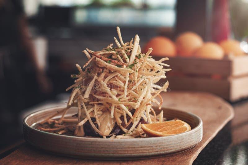 Bife meio-raro grelhado magro saudável servido com as microplaquetas de batata especiais do molho de mostarda na parte superior fotos de stock