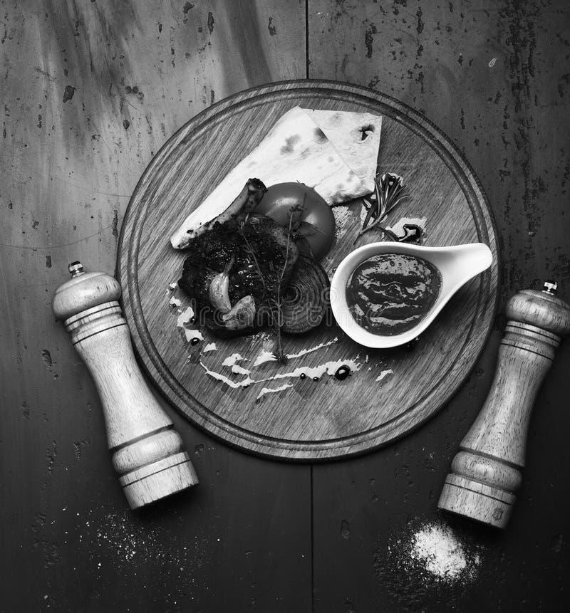Bife Roasted com tomate, flatbread e a cebola grelhada Reforços da carne de porco ou do cordeiro com molho de assado na placa de  imagens de stock royalty free