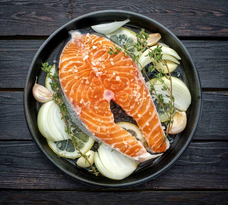 Bife salmon cru com ervas, cebola, alho e sal em um vintage foto de stock royalty free