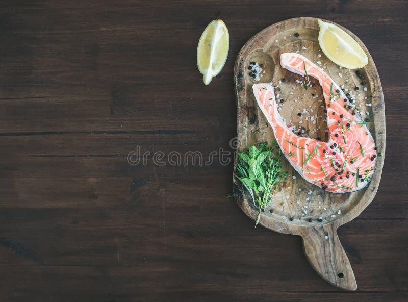 Bife salmon cru com ervas, o limão e as especiarias frescos no wo rústico imagens de stock