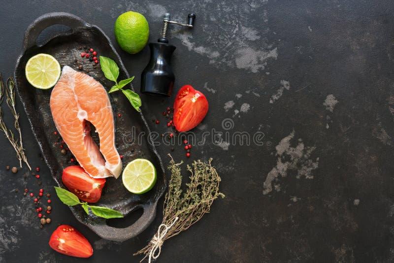 Bife Salmon cru com os ingredientes para cozinhar em um fundo de pedra preto Vista superior, espaço da cópia imagem de stock