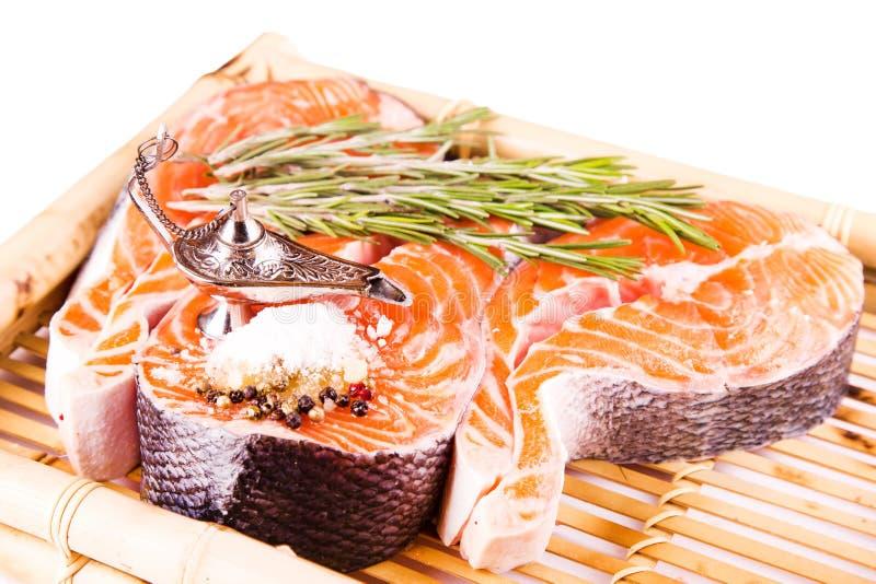 Bife salmon cru com rosemary em uma placa de bambu foto de stock
