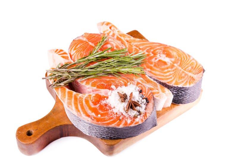 Bife salmon cru com rosemary em uma placa de madeira imagens de stock royalty free