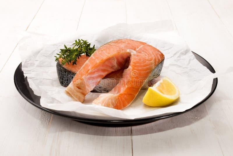 Bife salmon cru com tomilho e limão em uma placa fotos de stock
