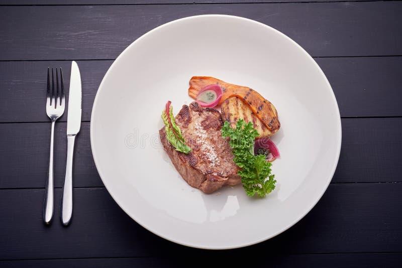 Bife suculento com batata e salada na placa branca imagens de stock royalty free