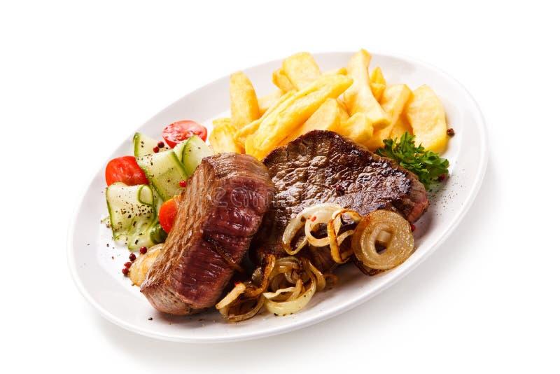 Bifes, batatas fritas e vegetais grelhados fotos de stock