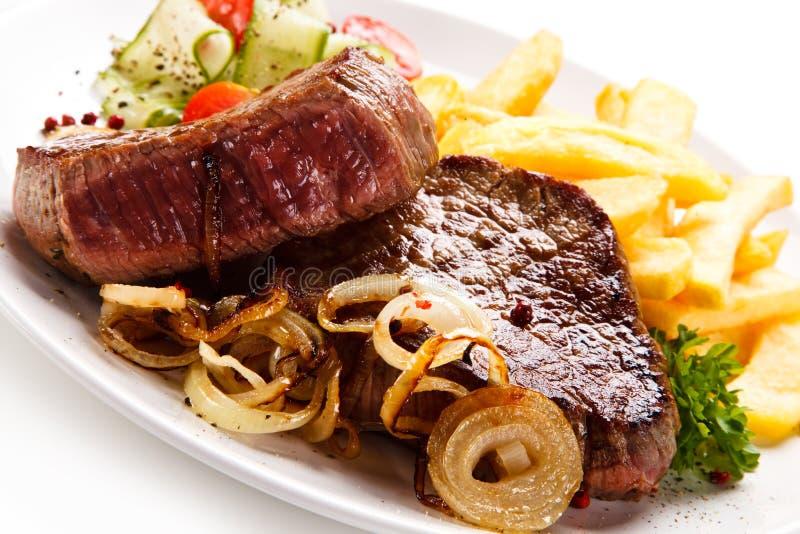 Bifes, batatas fritas e vegetais grelhados fotografia de stock