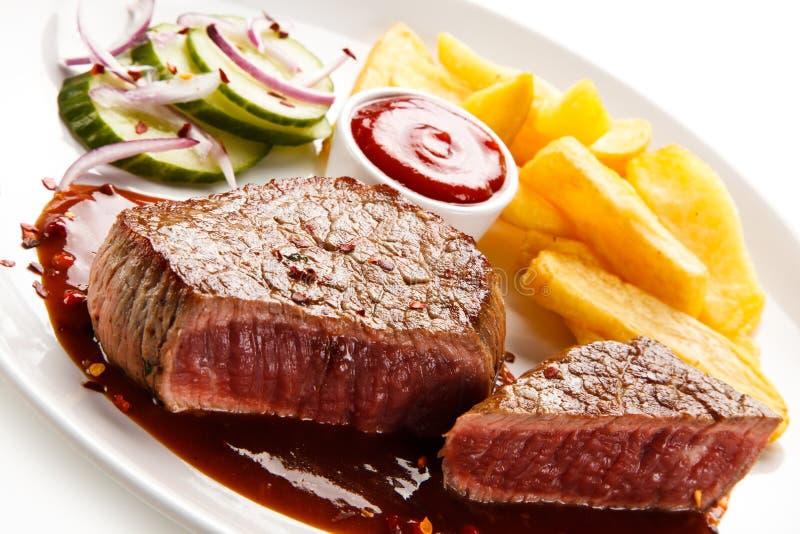Bifes, batatas fritas e vegetais grelhados imagens de stock
