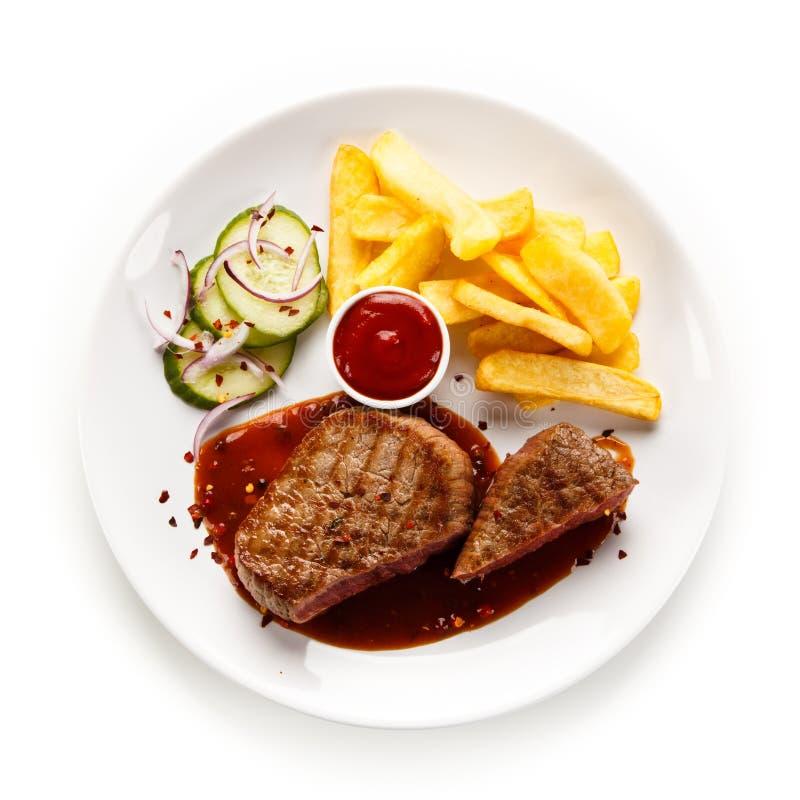 Bifes, batatas fritas e vegetais grelhados fotografia de stock royalty free