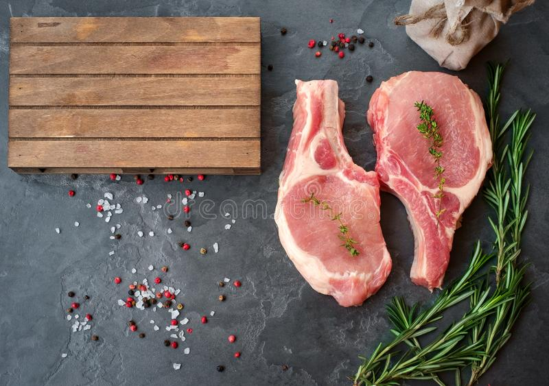 Bifes crus da carne de porco na opinião superior do fundo preto da pedra imagem de stock