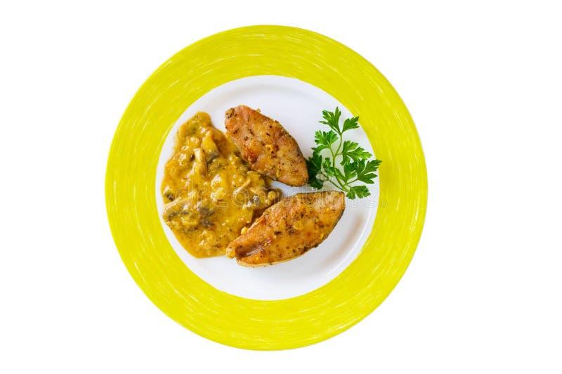 Bifes de peixes picantes fritados, servidos com molho de creme com cogumelos em uma placa cerâmica fotografia de stock