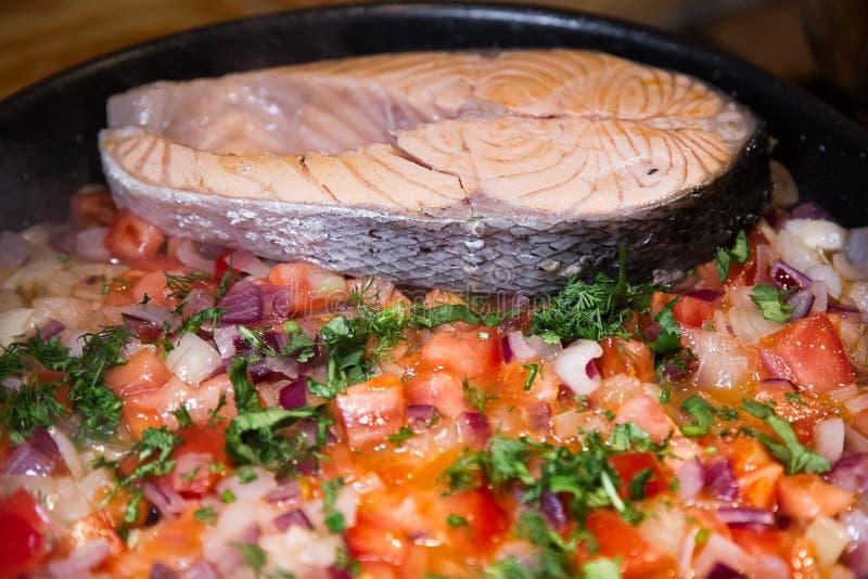 Bifes de salmões com a repreensão dos vegetais na frigideira fotografia de stock