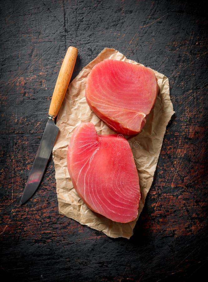 Bifes do atum cru fresco no papel com uma faca imagem de stock