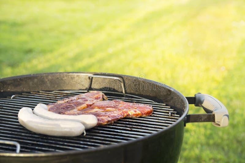 Bifes e salsichas da carne na grade foto de stock royalty free